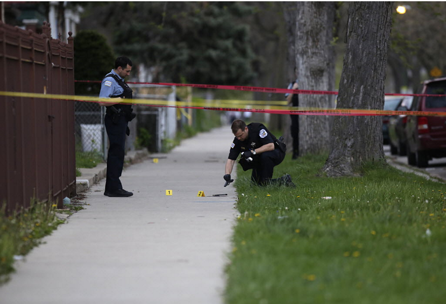 A Chicago Police Department officer watches as an evidence technician examines a gun at the scene of a fatal shooting in April. - JOSHUA LOTT/GETTY IMAGES