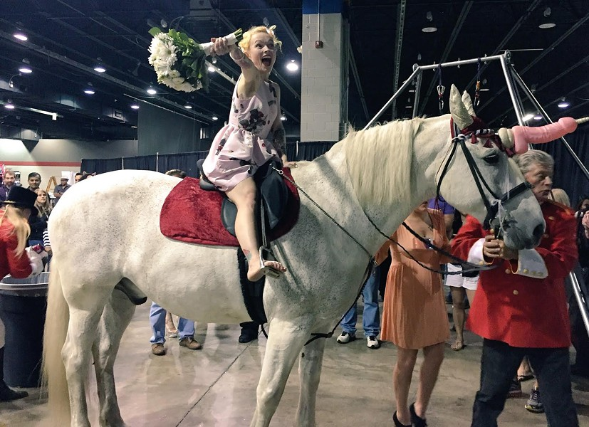 Adult film star Tita Cupcake DuJour on her penis unicorn as part of her wedding ceremony at Exxxotica - RYAN SMITH