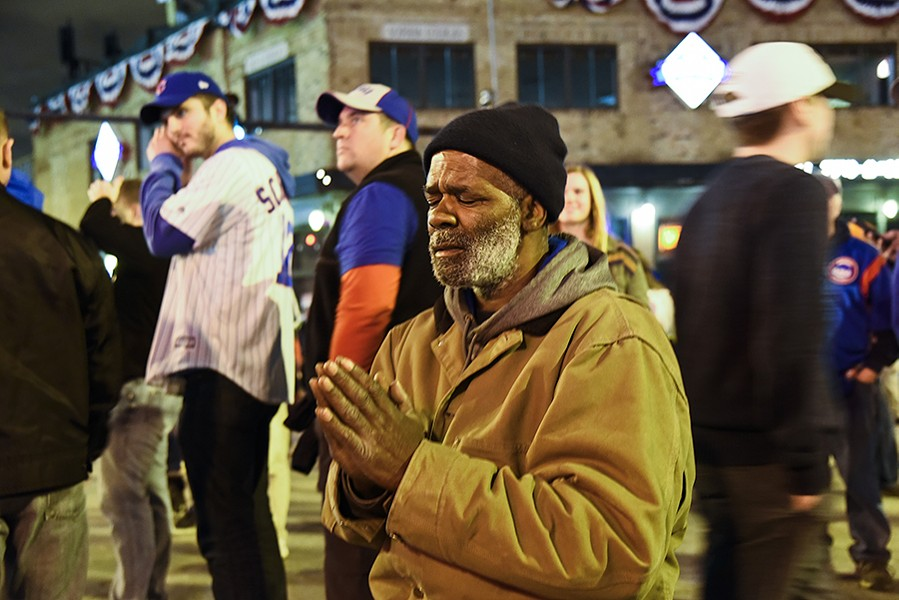 Chicago Cubs fan Wayne Tucker prays outside of Wrigley Field during the World Series. - MATT MARTON