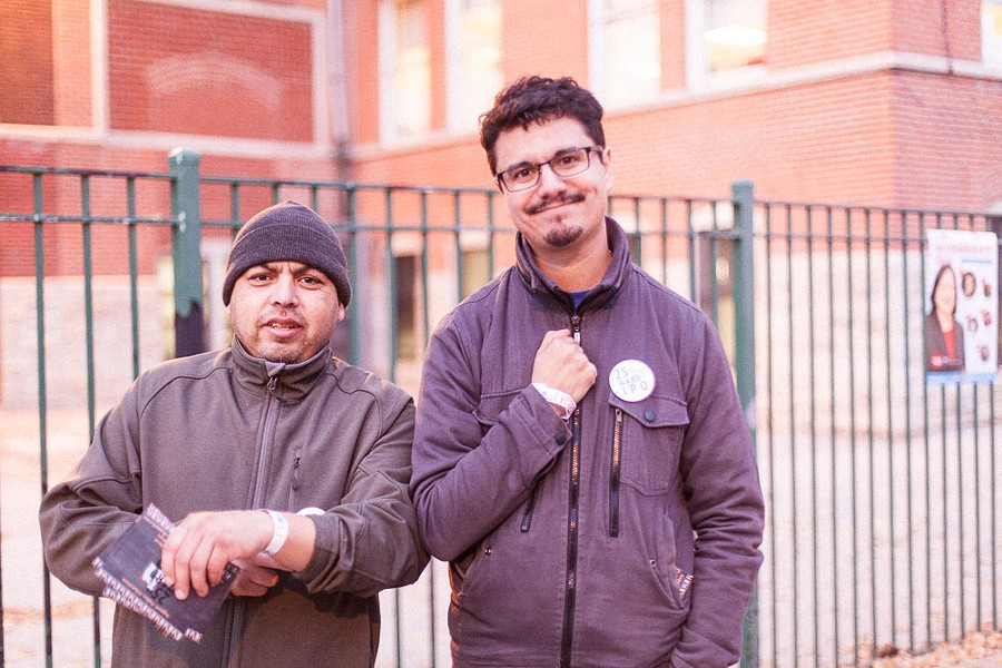 """25th Ward independent precinct organization volunteers Sergio Medina, left, and Jose Requena show off their """"I voted"""" bracelets at Cooper Dual Language Academy in Pilsen. - DANIELLE A. SCRUGGS"""