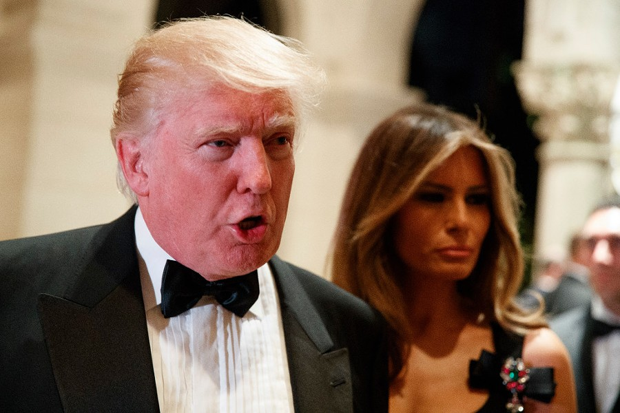 President-elect Donald Trump talks to reporters during a New Year's Eve party at Mar-a-Lago as his wife Melania Trump looks on. - AP PHOTO/EVAN VUCCI