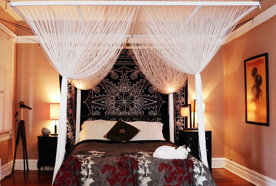 Master bedroom with a canopy of white string over the bed - MORGAN JOHNSON