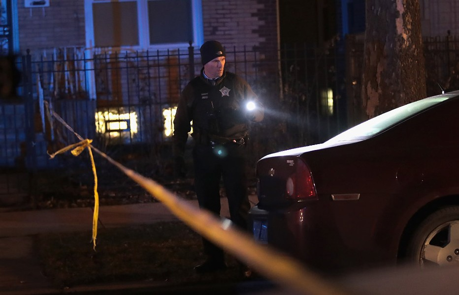 Police investigate the scene of a January 1 shooting in which a 23-year-old woman was shot in the chest and hand and a 25-year-old man was shot in the leg. - PHOTO BY SCOTT OLSON/GETTY IMAGES