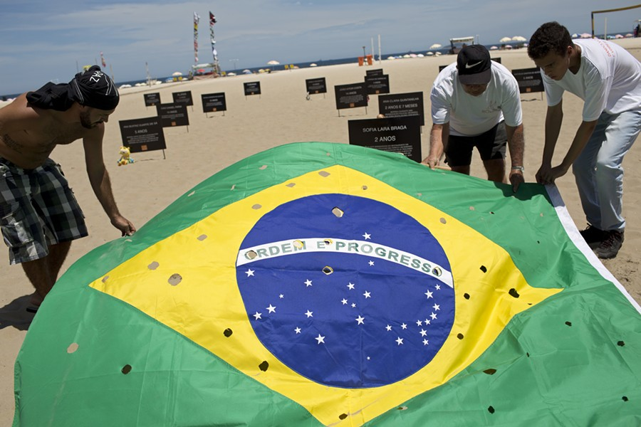 Activists lay out a Brazilian flag, punctured to symbolize bullet holes, on Copacabana beach in Rio de Janeiro, during a protest calling for an end to the violence that erupts during police operations against suspected drug traffickers. - AP PHOTO/SILVIA IZQUIERDO