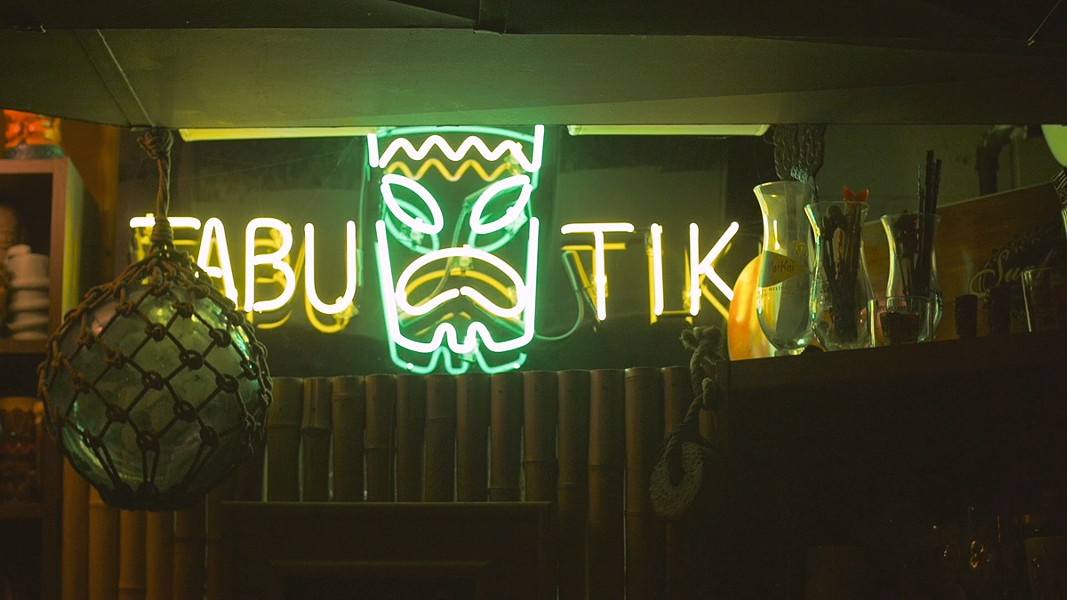 A neon sign marks the Tabu Tiki Room, the Carters' basement bar. - KERRI PANG
