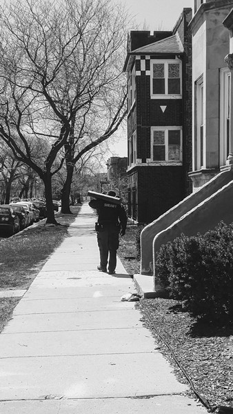 A Cook County sheriff's deputy strolls outside a south-side building with a battering ram, which deputies use to enter units if tenants being evicted aren't home and the landlord doesn't have a key. - MAYA DUKMASOVA