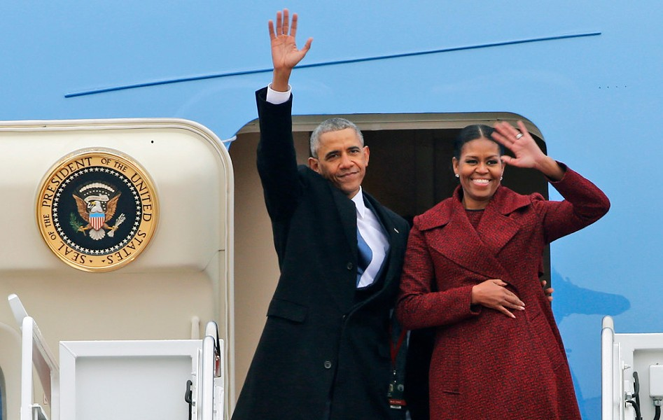 Former president Barack Obama and former first lady Michelle Obama wave to the crowd as they board an air force jet in January. - AP PHOTO/STEVE HELBER