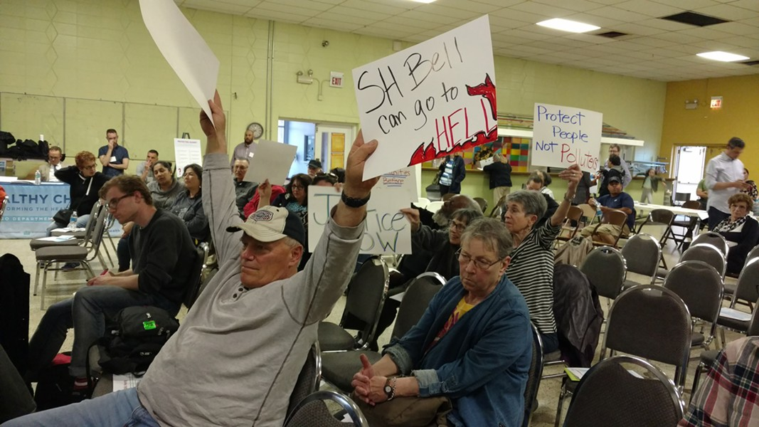 Though the crowd thinned out by the end of the meeting, some residents remained till the end, brandishing homemade signs and calling government officials to shut down S.H. Bell's manganese storage and transportation operations - MAYA DUKMASOVA