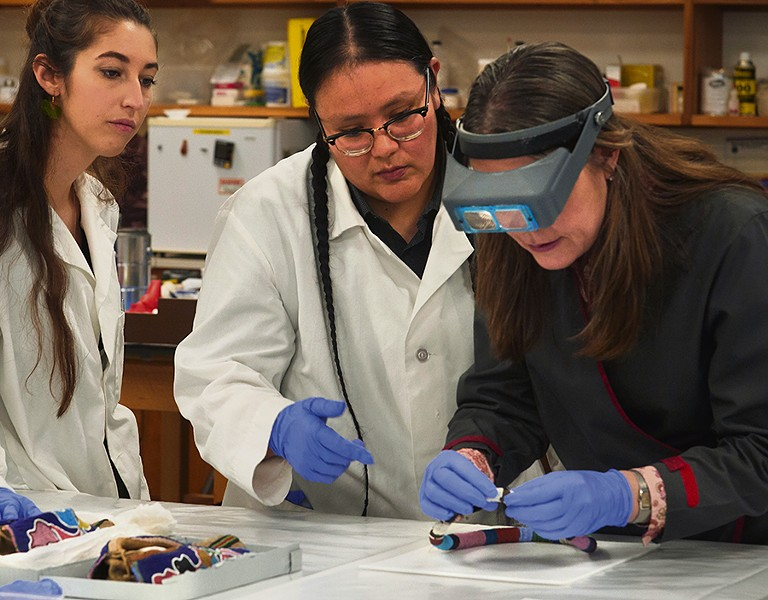 Lead conservator Stephanie Hornbeck (right) with conservation technicians J. Kae Good Bear (center) and Ellen Jordan (left) work in the Regenstein Lab. - JOHN WEINSTEIN