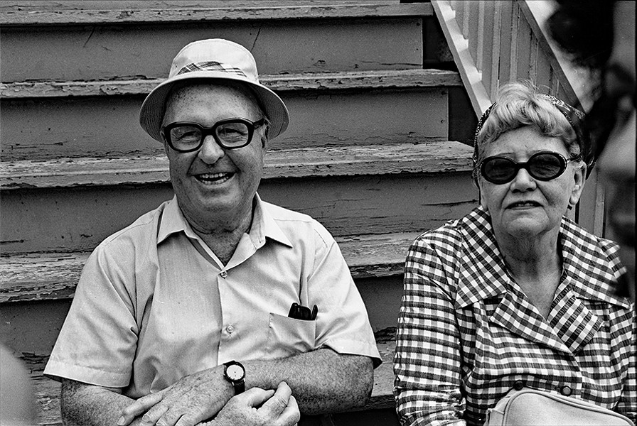 A couple enjoys the view of the parade from the comfort of their stairs. - DIANE ALEXANDER WHITE