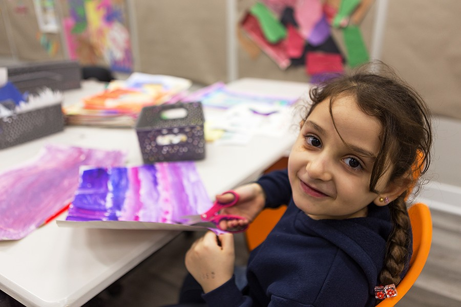 Fatima, 6, cuts out shapes of jasmine leaves from watercolor drawings she created. Fatima and her family moved to Chicago from Syria about three years ago. - FARAH SALEM FOR CHICAGO READER