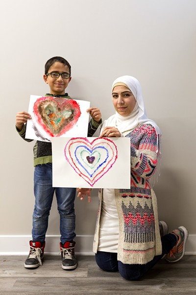 Hozaifa, 7, and his mother present a heart he drew using salt and watercolors. Hozaifa's mother is also an employee at Syrian Community Network. They moved to Chicago from Syria about three years ago. - FARAH SALEM FOR CHICAGO READER