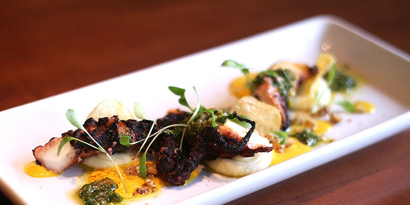 Grilled octopus, pommes puree, aji amarillo vinaigrette, fingerling potato chips, walnut pieces, baby cilantro, and freeze-dried aji amarillo powder