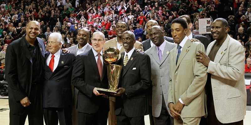 Members of the 1990-'91 Chicago Bulls celebrate the 20th anniversary of their championship season during halftime of a March 2011 game. Hodges, center, holds the trophy.