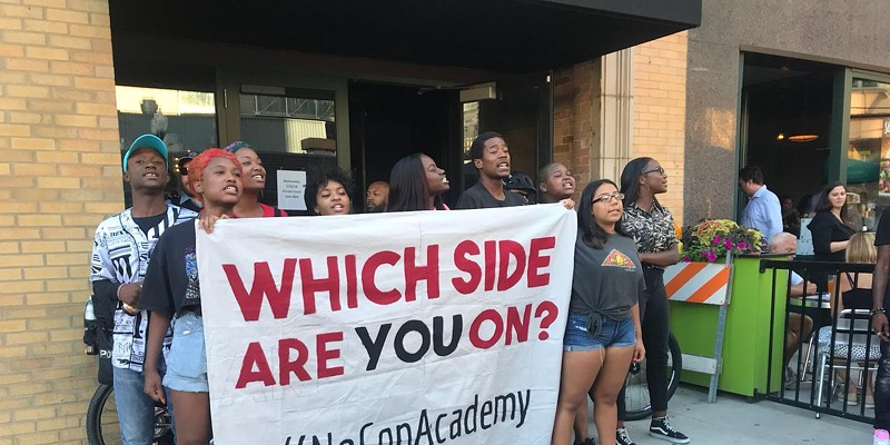 Protesters with the #NoCopAcademy campaign stage a die-in outside the Aldermanic Black Caucus's annual fund-raiser.