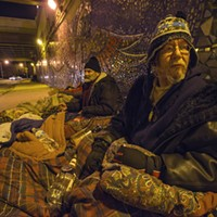"Home sweet home for the homeless ""Indian Pete,"" 51, sits under the Foster Avenue viaduct near the lakefront with his friend Gus, 55. City officials and alderman James Cappleman have long clashed with advocates over attempts to move ""homeless"" residents from this and other Uptown viaducts. Pete, a member of the Ojibwe tribe, dryly notes that the tile mosaic under the viaduct celebrates Native American heritage."