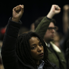 Attendees raise their fists in protest during the November Police Board meeting Thursday.
