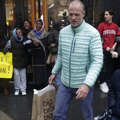 Shoppers walk past demonstrators blocking the entrance to the Michigan Avenue Under Armour store on Black Friday.