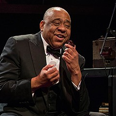 Louis Armstrong takes a complex solo in Court Theatre's Satchmo at the Waldorf