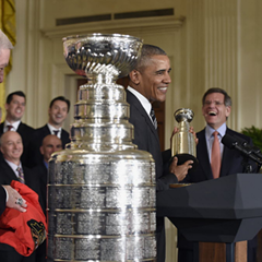 President Obama, flanked by Blackhawks president John McDonough, left, and chairman Rocky Wirtz, holds up a small version of the Stanley Cup during a ceremony at the White House Thursday.