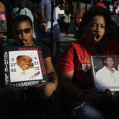 Antoinette Marshabanks, left, holds a photos of her son Archie Lee Chambers Jr. and Sharon Miles holds a picture of her son Korey Parker during a sit-in as they protest the recent rise in homicides across the city.