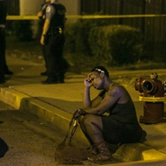 A woman sits on the curb as police investigate an August scene where gunfire at a birthday party left a man dead and a woman injured.