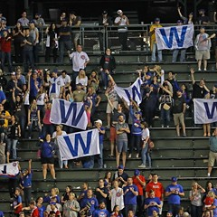 Fans in the bleachers hold W flags after the Cubs beat the Cincinnati Reds Wednesday.