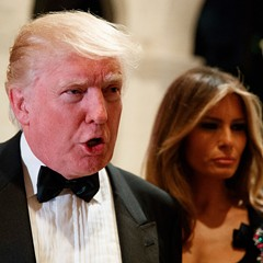 President-elect Donald Trump talks to reporters during a New Year's Eve party at Mar-a-Lago as his wife Melania Trump looks on.