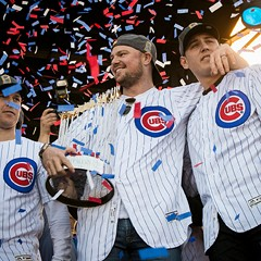 Jon Lester, flanked by Chris Coghlan and Anthony Rizzo, holds the Commissioner's Trophy during the Chicago Cubs' World Series rally in Grant Park.