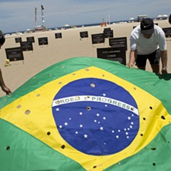 Activists lay out a Brazilian flag, punctured to symbolize bullet holes, on Copacabana beach in Rio de Janeiro, during a protest calling for an end to the violence that erupts during police operations against suspected drug traffickers.