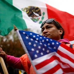A protester holds U.S. and Mexico flags during May Day demonstrations in Chicago.