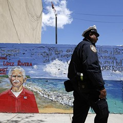 A police officer walks by a mural of Oscar López Rivera in New York.