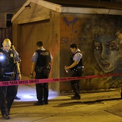 Police officers investigate the crime scene where a man was shot in the alley in the Little Village neighborhood in Chicago on July 2.