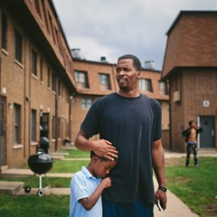 Lamont Anderson embraces his son, eight-year-old Lamont Jr. Lamont Jr.'s blood lead levels tested above the CDC's cutoff for lead poisoning. After living in the complex for more than a decade, the family moved to Gary, Indiana, last summer.
