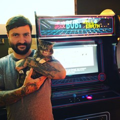 Mike Bridavsky and Lil' Bub pose with the arcade game Hello Earth at Logan Arcade.