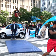 The Jesse White Tumblers jump over Car2go CEO Olivier Reppert's head at the launch.