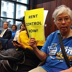 A member of the Jane Addams Senior Caucus listens to state senate testimony about a bill that would enact rent regulation in Illinois