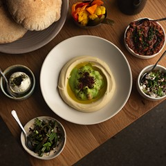 Salatim (clockwise from top): Yemeni, Bulgarian, and Israeli pickles; ezme; cipollini onions with Bulgarian feta; wood-roasted summer beans; labneh; (center) masabacha hummus with house-made pita