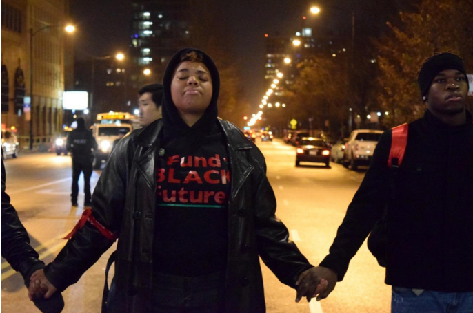 Activists joined hands at Roosevelt and Halsted before marching through the city streets November 24. - MARTIN MACIAS