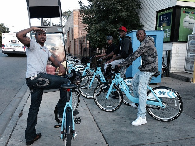 Friends check out Divvy bikes in East Garfield Park on one of three days in September when day passes were free. - JOHN GREENFIELD