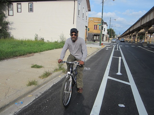Housepainter James Woods rides in the Lake Street protected bike lane on the west side in September 2014. - JOHN GREENFIELD