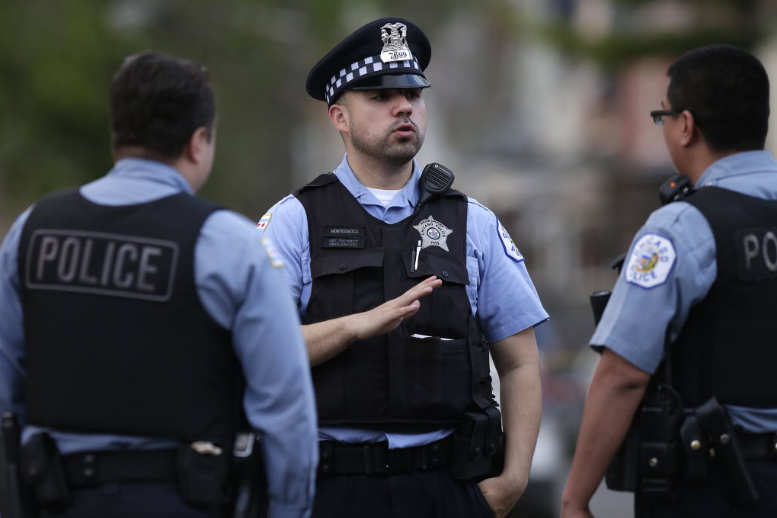 Chicago Police stand near the scene of a fatal shooting on April 25. - JOSHUA LOTT/GETTY IMAGES