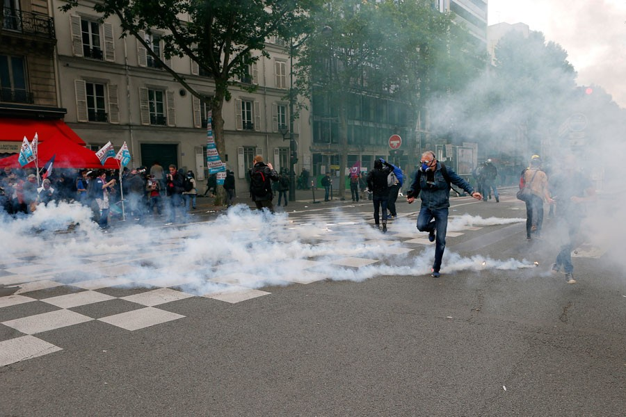 A man throws smoke during a demonstration in Paris Tuesday. - FRANCOIS MORI/AP