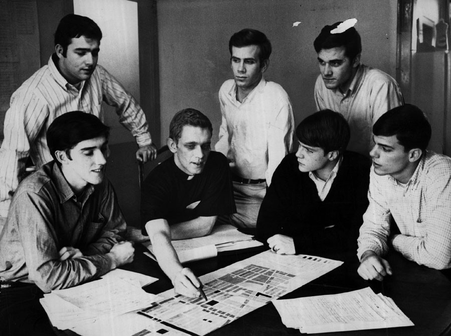 "Jesuit seminarian John R. ""Jack"" Macnamara huddles with college students helping him combat inflated property contracts in North Lawndale in May 1968. - SUN-TIMES PRINT COLLECTION"