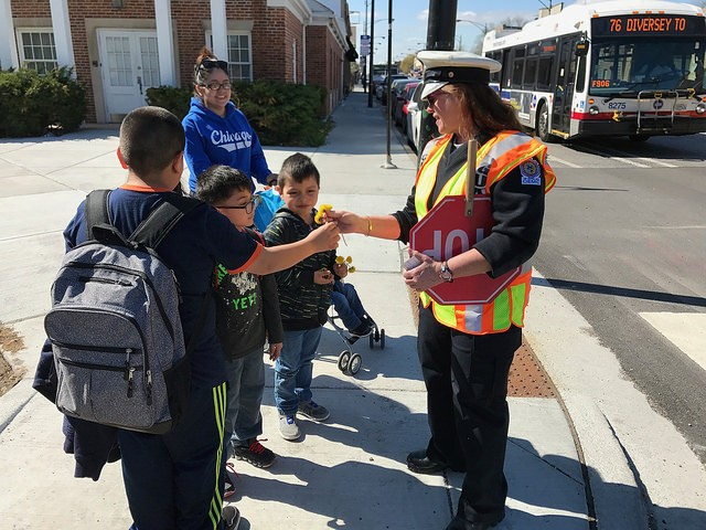 Ana the crossing guard gets dandelions from Murphy Elementary students. - JOHN GREENFIELD