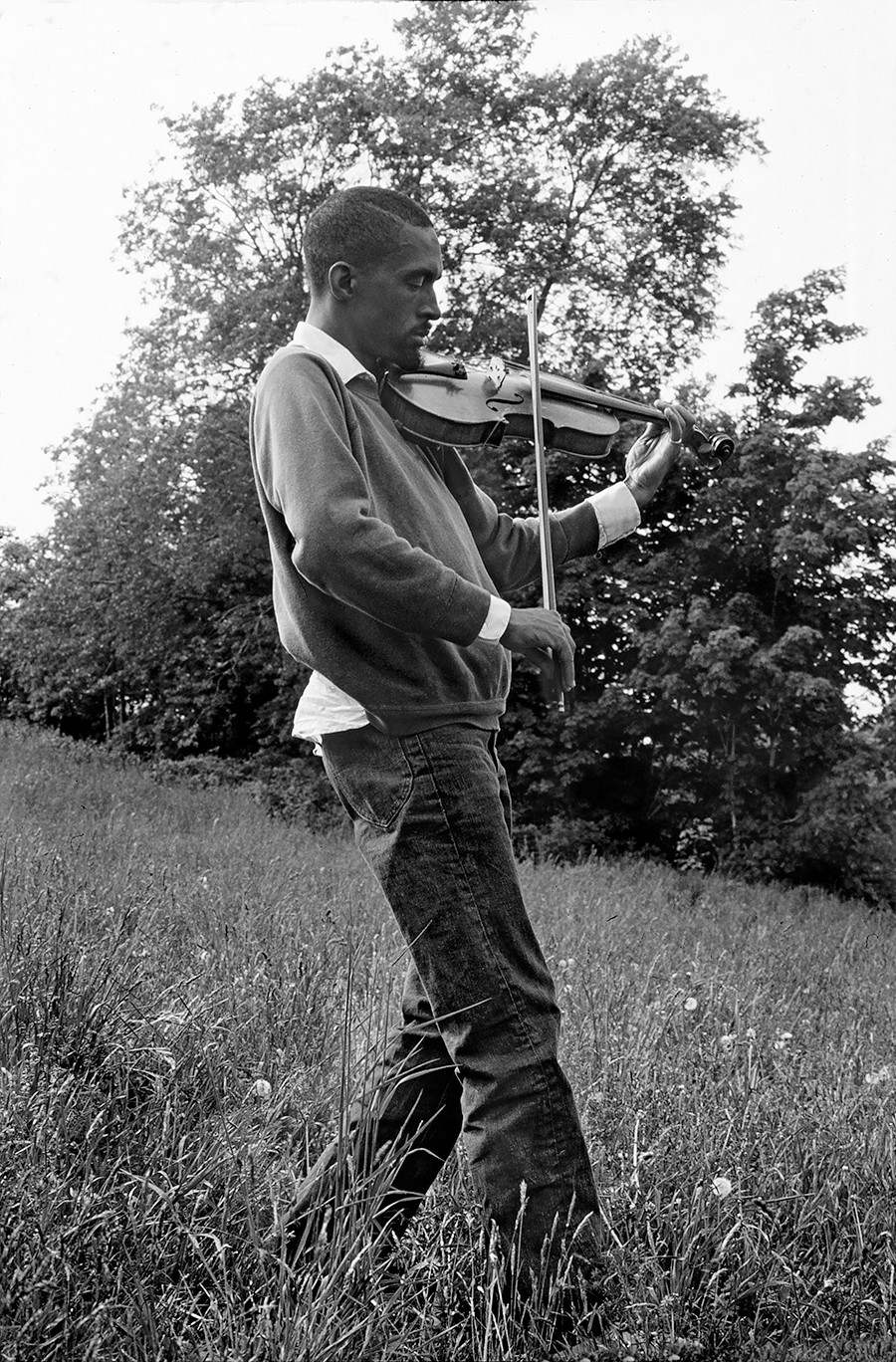 Julius Eastman plays the violin at Griffis Sculpture Park in East Otto, New York, during a 1975 rehearsal by theS.E.M.Ensemble. - CHRIS RUSINIAK