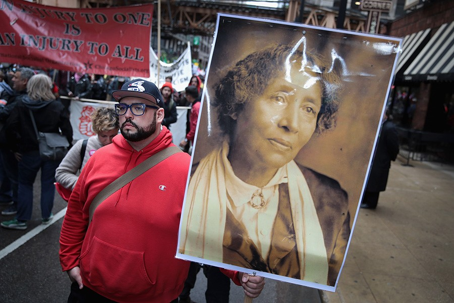 A demonstrator at a downtown Chicago march on May 1, 2017, celebrates May Day (also known as International Workers' Day) by carrying a portrait of IWW cofounder Lucy Parsons. - SCOTT OLSON
