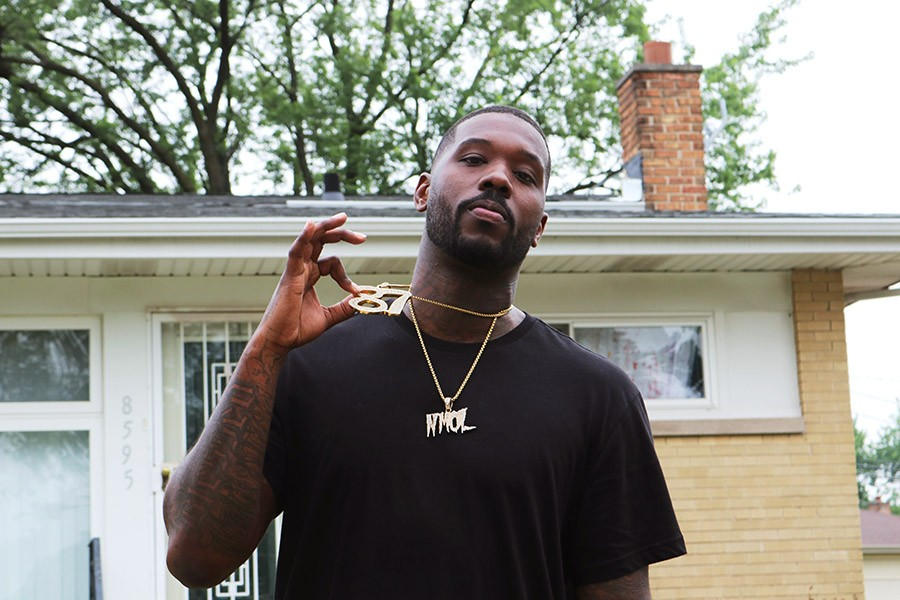 "Phor in front of what used to be his grandma's house in Marynook. His ""87"" chain represents nearby 87th Street as well as his birth year, and ""NMOL"" stands for ""No more ordinary lifestyle."" - MORGAN ELISE JOHNSON"