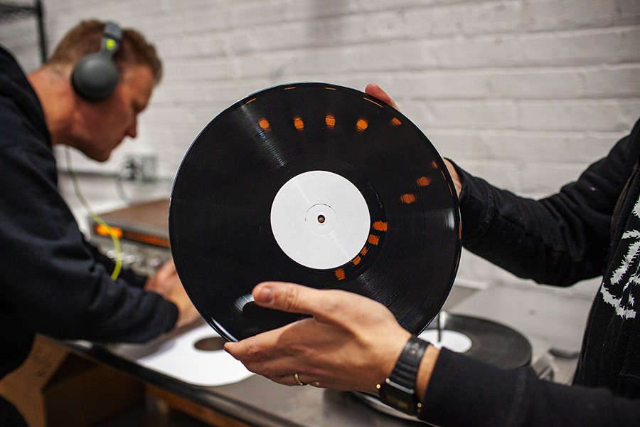 Andy Weber of Smashed Plastic listens for imperfections in a test pressing while his colleague John Lombardo examines another copy by eye. - ADAM JASON COHEN