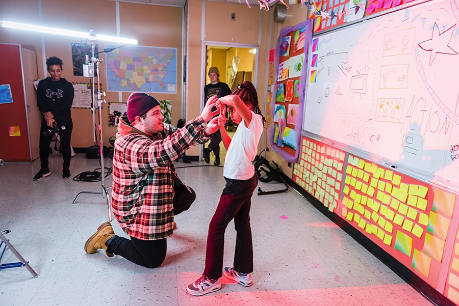 Connor Wiles shows nine-year-old Danielle Reed, who plays the director of the video, how to frame a shot with her hands. - ALLISON ZIEMBA